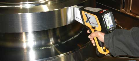 Olympus Innov-X DELTA Premium XRF alloy analyzer testing a stainless steel fixture for quality control